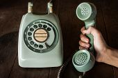 Close Up Of Hand Holding Old Black Rotary Telephone With Dust On Telephone On Wooden Retro Table. Ol poster