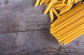 Постер, плакат: Macaroni Pasta Spaghetti On A Wooden Background