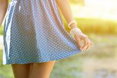Beautiful young woman wear in a short dress. Girl holding hand edge of the skirt , close-up on green poster