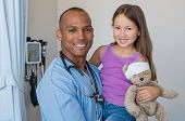 Happy male nurse carrying cute girl in hospital room. Doctor with stethoscope and little patient loo poster