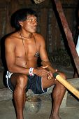 KAMAYURA VILLAGE, BRAZIL - MAY 18: Member of a threatened Indian tribe, the Kamayura, playing a sacr