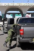 An army soldier checking vehicles traveling from Mexico to the U.S. on a checkpoint in Ciudad Juarez