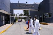 MEXICO CITY - APRIL 28: Hospital workers walk past the main entrance of the Mexican Institute of Res
