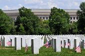 Gravestones decorated with U.S. flags to commemorate Memorial Day at the Arlington National Cemetery in Arlington, Virginia, near Washington DC, with Pentagon in the background.