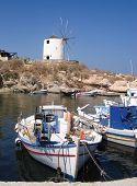 Greek fishing boats and windmill against clear blue sky, Paros, Greek Islands, Greece
