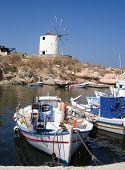 Greek fishing boats and windmill against clear blue sky, Paros, Greek Islands, Greece