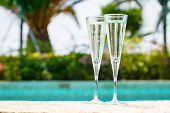Two Glasses Of Prosecco   At The Edge Of A Resort Pool. Concept Of Luxury Vacation poster