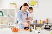 family, food, healthy eating, cooking and people concept - happy mother adding chopped vegetables to poster