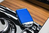 Closeup Inside Vehicle Of Wireless Blue Leather Key Ignition On Natural Wood Panel. Wireless Start E poster