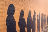 A Line Of Shadows Of People Lined Up Against A Red Brick Wall. Stand In A Queue To The Changes poster