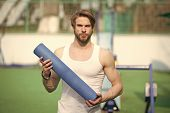 Practicing Yoga. Sportsman Carries Yoga Mat For Outdoor Practicing. Outdoor Yoga Concept. Man Athlet poster