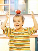 Adorable Boy Balancing A Red Apple