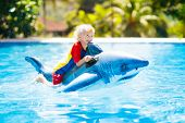 Child Playing In Swimming Pool. Kids Learn To Swim. Little Baby Boy With Inflatable Toy Float Playin poster