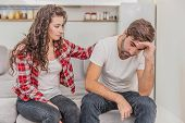 Couple Argue. The Wife Shouted To Her Desperate Husband, Sitting On The Couch In The Living Room At  poster