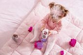 High Angle View Of Baby Girl Wearing Pink Tutu Skirt, Sitting On A Duvet And Playing With Her Shoes  poster