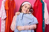 Happy Smiling Woman Chooses Blouse. Satisfied Lady Likes Purchase. Brunette Embraces Hanger With Blu poster