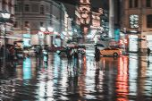 City Street In Rainy Night, Abstract Bright Blurred Background With Unidentified People. Vivid Illum poster