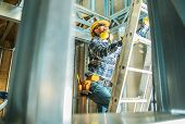 Skeleton Steel Building Construction Worker Wearing Safety Hard Hat And Noise Reduction Headphones.  poster