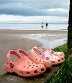 Two pairs of rubber slip on shoes on groyne