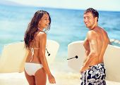 Surfers on beach having fun in summer. Surfer woman and man with boogieboard smiling happy on beach  poster