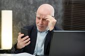 A Senior Businessman Using  Smartphone, He Is Having Difficulties And Vision Problems poster