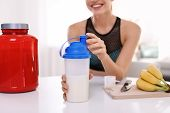 Young Woman Holding Bottle Of Protein Shake At Table With Ingredients In Room, Closeup poster