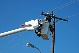 stock photo of power lines  - A picture of a man in a bucket lift repairing a power line - JPG