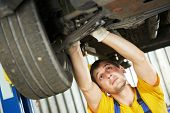 car mechanic examining car suspension of lifted automobile at repair service station