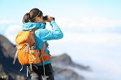 stock photo of binoculars  - Hiker looking in binoculars enjoying spectacular view on mountain top above the clouds - JPG