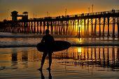 Silhouetted surfer at Oceanside Pier, Oceanside, California, USA.