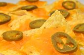 image of nachos  - Focus on one nacho on plate of nachos - JPG