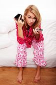 Disgruntled young woman in her pyjamas sitting on the edge of her bed changing TV channels