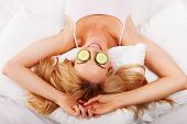 Woman reclining on her back on her bed using cucumber eyepads made of fresh sliced cucumbers to soot