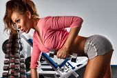 Woman with dumbbells in sport center