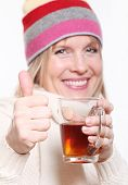 Mid age Woman With Hot tea Wearing Winter Clothes showing thumbs up on a white background