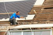 stock photo of shingle  - worker on roof at works with flex tile material demounting roofing - JPG