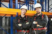Two warehouse installation staff male workers in uniform in front of pallet rack arrangement stillages