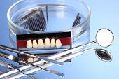 picture of prophylactic  - denture with dental tools on blue background - JPG