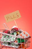 shopping trolley with pills, on red background