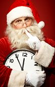 stock photo of shhh  - Photo of Santa holding clock showing five minutes to midnight and making shhh gesture - JPG