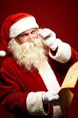 image of letters to santa claus  - Portrait of happy Santa Claus holding Christmas letter and looking at camera - JPG