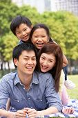 Young Chinese Family Relaxing In Park Together