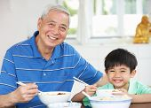 Portrait Of Chinese Grandfather And Grandson Eating Meal Together