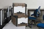 View of moving boxes by chairs on office desk