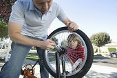 Closeup of a cropped father fixing son's bicycle tyre