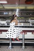 Full length side view of a young woman sitting at the diner counter