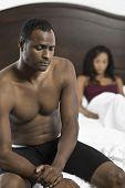 Tensos sin camisa hombre afroamericano sentado en cama con una mujer borrosa en fondo