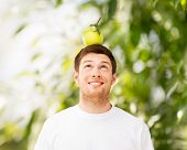 happy young man with green apple on his head