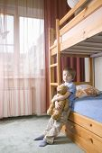 Full length of bored young boy with teddy bear leaning on bunk bed