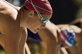 Closeup side view of female swimmers at the starting blocks